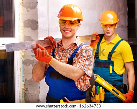 Happy group people men in builder uniform indoor. - stock photo