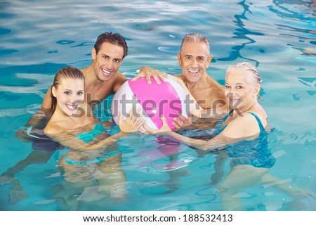 Happy group playing in swimming pool with a water ball in summer - stock photo