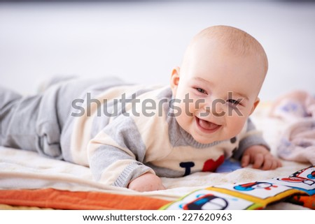 Happy gurgling baby lying on his bed playing with colorful pictures in a book looking at the camera with an adorable beaming smile of contentment - stock photo