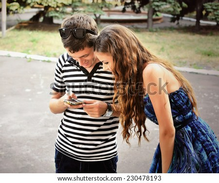 Happy guy and girl  looking at mobile phone  - stock photo
