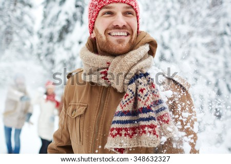 Happy guy in winterwear on background of his friends - stock photo