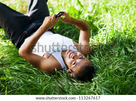 happy guy lying on the grass and listening to music - stock photo