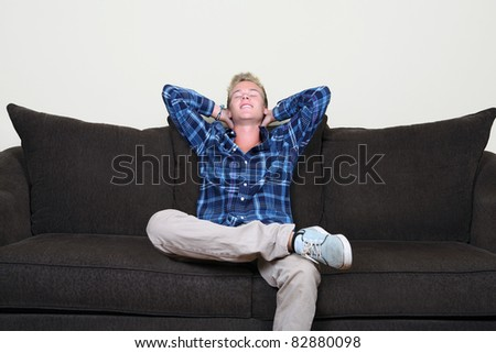 Happy guy on couch - stock photo