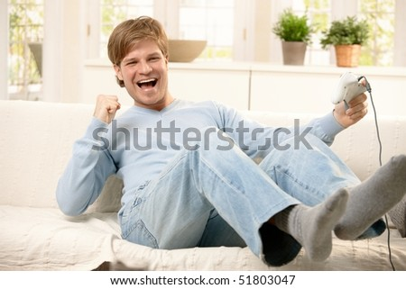 Happy guy playing computer game, holding controller, laughing on living room sofa. - stock photo