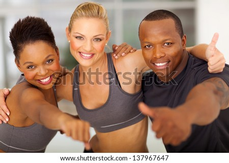 happy gym team giving thumbs up - stock photo