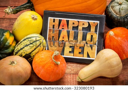 Happy Halloween - abstract text in letterpress wood type on a digital tablet surrounded by pumpkin and winter squash - stock photo