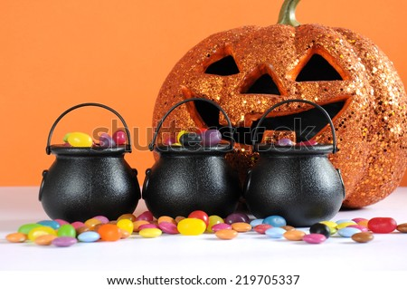Happy Halloween candy in trick or treat carry cauldrons with pumpkin on orange background. - stock photo
