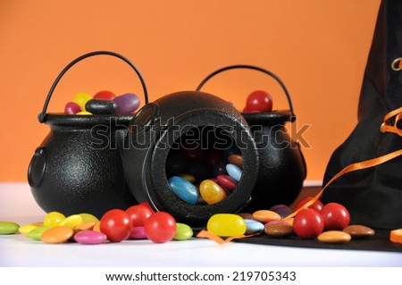Happy Halloween candy in trick or treat carry cauldrons with witches hat on orange background. - stock photo