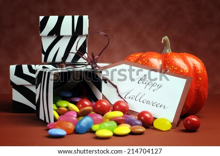 Happy Halloween trick or treat black and white zebra candy boxes with bright colorful candy, gift tag and orange pumpkin. - stock photo