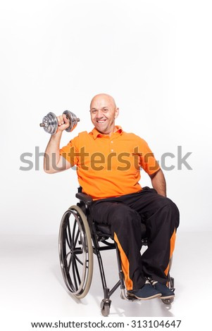 Happy handicapped person on a wheelchair with a dumbbell in the hand isolated on white - stock photo