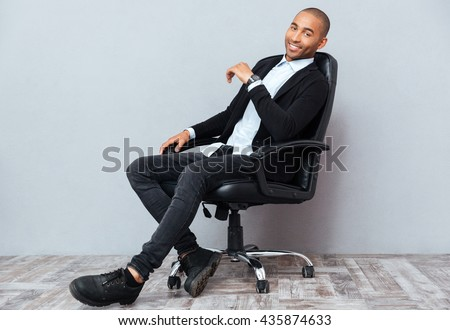 Happy handsome african american young man sitting in leather office chair - stock photo