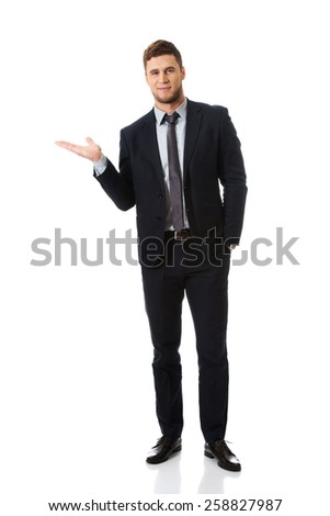 Happy handsome businessman holding copyspace on palm. - stock photo