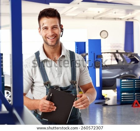 Happy handsome caucasian male car mechanic at auto repair business shop. Wearing workwear clothes and wireless headset, smiling, standing, looking at camera. Greasy, dirty, tablet computer in hand. - stock photo