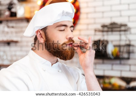 Happy handsome chef cook smelling aroma of food on the kitchen  - stock photo