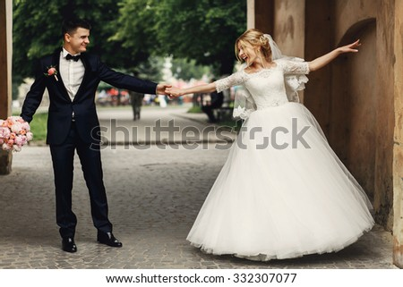 Happy handsome groom and blonde beautiful bride in white dress dancing under arc - stock photo