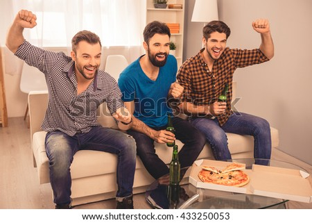 Happy handsome group of men watching sport tv with beer and pizza - stock photo