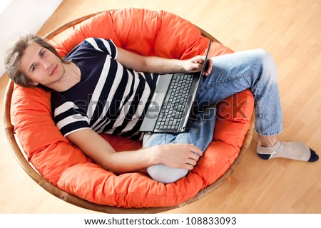 Happy handsome guy relaxing with laptop at home - stock photo