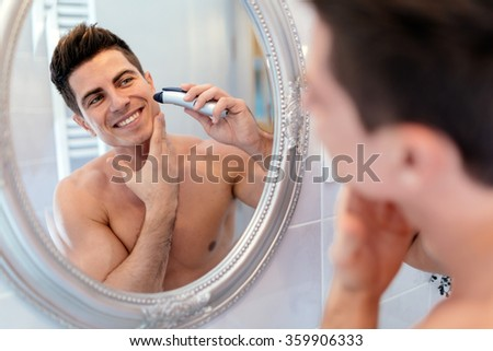 Happy handsome man shaving in bathroom - stock photo