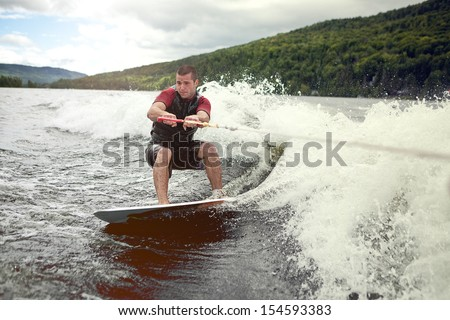 Happy handsome man wakesurfing in a lake and pulled by a boat. - stock photo