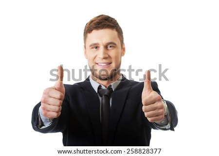 Happy handsome smiling businessman with thumbs up gesture. - stock photo