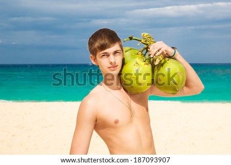 Happy handsome young male beach smiling at camera holding coconuts under the sun on sunny summer day during holidays vacation. Good looking guy in his 20s. - stock photo