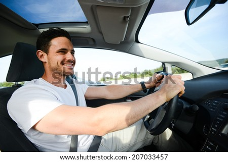 happy handsome young man driving his new car on highway  - stock photo