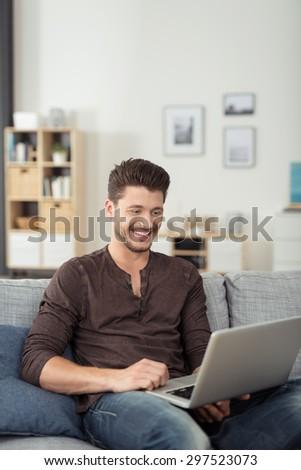 Happy Handsome Young Man Using her Laptop Computer While Relaxing on the Couch at the Living Room. - stock photo