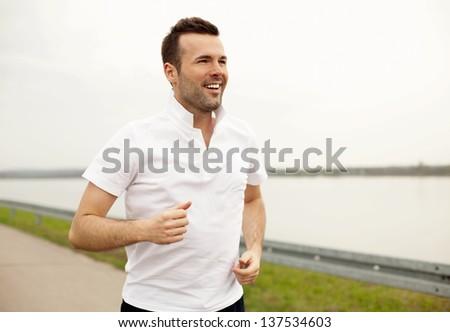 Happy hansome man running - stock photo