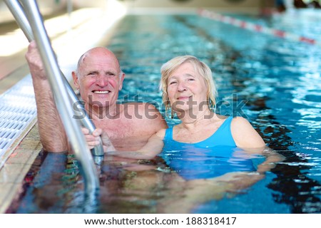 Happy healthy active senior couple having fun together in the swimming pool  - stock photo