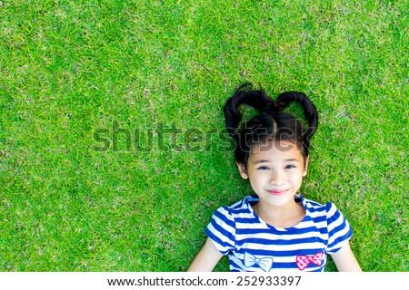 Happy healthy Asian kid with heart-shaped hair lying on the grass field background: Little girl child in beautiful green environment: Peaceful mind girl in clean natural greenery surroundings - stock photo