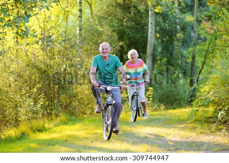 Happy healthy couple biking together in the forest. Seniors enjoying sunny day outdoors. Active retirement concept. - stock photo
