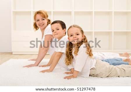 Happy healthy family making gymnastic exercises together - focus on the little girl - stock photo