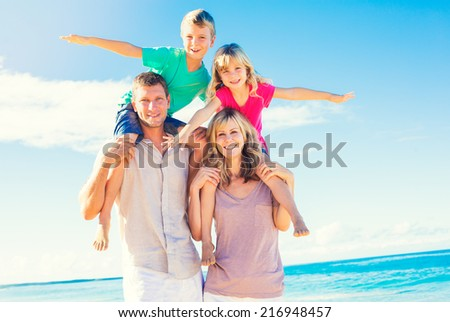 Happy Healthy Family of Four having Fun on Tropical Beach - stock photo