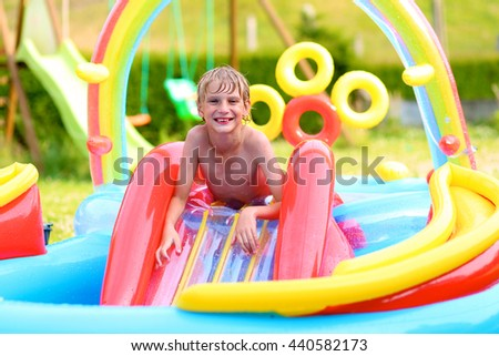 Happy healthy kid having fun in inflatable play center. Child enjoying summer holidays playing in the pool at the backyard in the garden. Schoolboy relaxing on hot sunny day. - stock photo