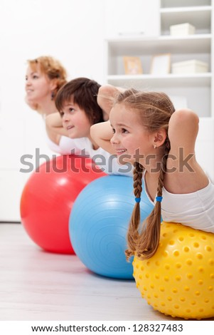 Happy healthy kids exercising together with their mother - stock photo