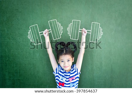 Happy healthy strong super powerful kid weight lifting exercise on grunge green chalkboard background: World health day WHD JA: Gender parity on human rights Children's day concept Women's leader idea - stock photo