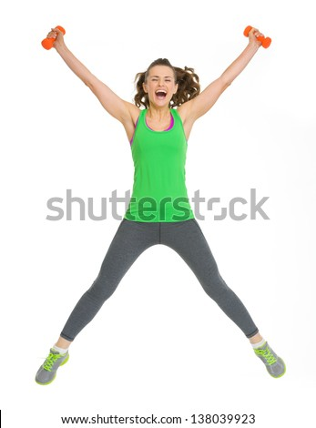 Happy healthy young woman with dumbbells jumping - stock photo