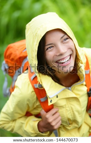 Happy hiker woman hiking in rain with backpack smiling candid and real. Fresh girl trekking in autumn forest. Beautiful smile on mixed race Asian Caucasian female model. - stock photo