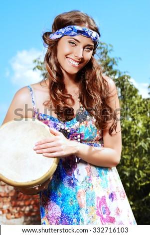 Happy hippie girl playing her drum outdoor.  - stock photo
