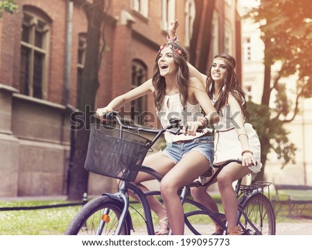 Happy hippie woman riding a tandem in the park  - stock photo