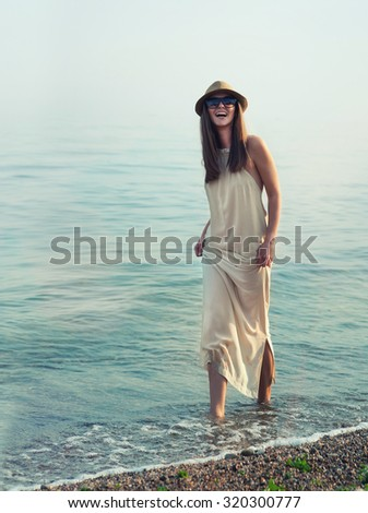 Happy hipster girl walking in sea water. - stock photo