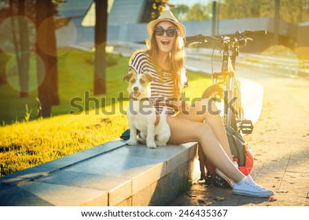 Happy Hipster Girl with her Dog and Bike in the City. Toned and Filtered Photo. Modern Youth Lifestyle Concept. - stock photo