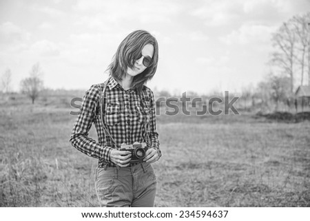 Happy hipster girl with vintage photo camera on nature. With film grain and low contrast effect. Black-white photo. - stock photo