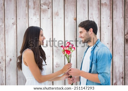 Happy hipster giving his girlfriend roses against wooden planks - stock photo