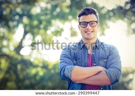 Happy hipster looking at camera on a sunny day - stock photo
