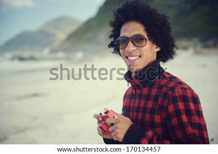 Happy hipster man smiling with toy camera at the beach - stock photo