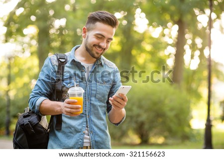 Happy hipster man walking in autumn park and smiling. Short-haited man looking at mobile phone's screen and enjoying reading messages. - stock photo