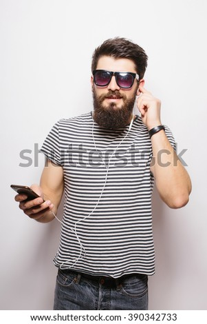 Happy Hipster with beard wearing  shirt and sunglasses enjoying music against white background - stock photo