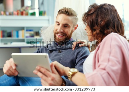 Happy hipster with girlfriend looking on tabelt - stock photo