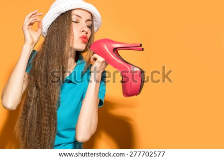 Happy hipster woman holding high heels over vibrant orange background - stock photo